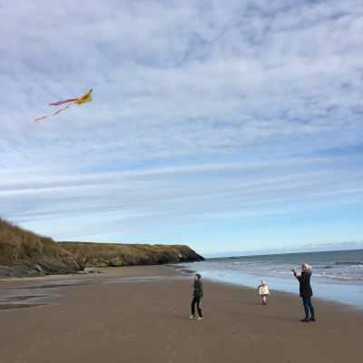 WellNow Co Flying Kite on beach in winter Health Coach